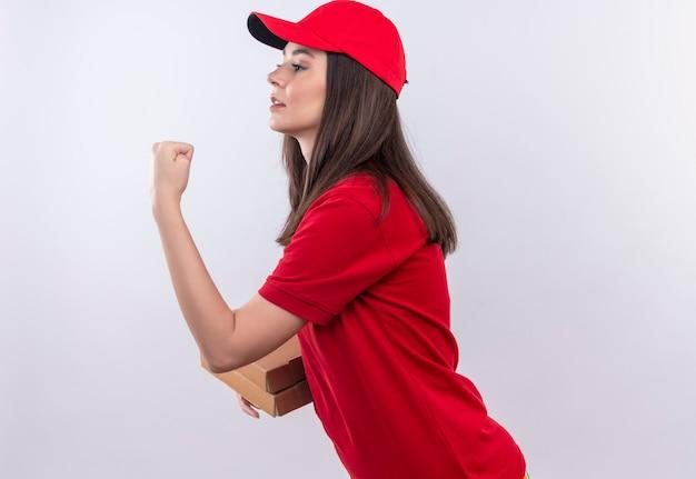 Молодая доставщица в красной футболке в красной кепке держит коробку для пиццы и показывает кулак на изолированном белом фоне
