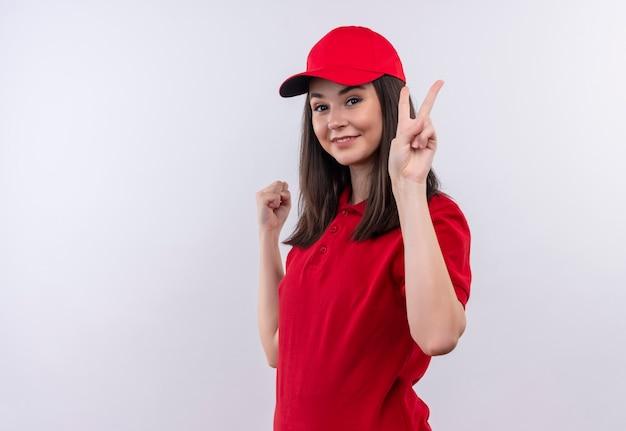 Молодая доставщица в красной футболке в красной кепке показывает жест на изолированном белом фоне