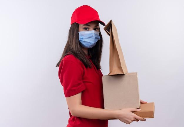 Молодая доставщица в красной футболке в красной кепке носит маску для лица, держащую коробку и коробку для пиццы и пакет на изолированном белом фоне
