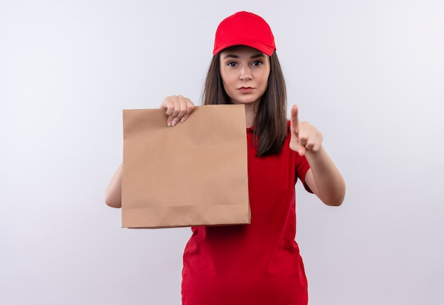 Young delivery girl wearing red t-shirt in red cap holding package and points to ahead on isolated white background