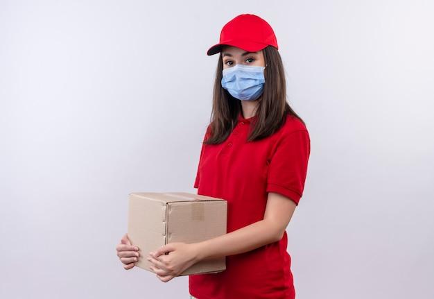 La giovane ragazza di consegna che porta la maglietta rossa nel cappuccio rosso indossa la maschera per il viso in possesso di una scatola su sfondo bianco isolato