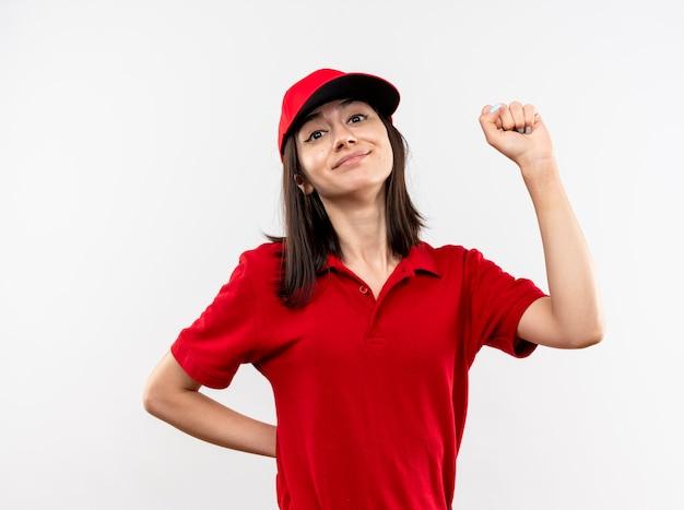 빨간 유니폼을 입고 젊은 배달 소녀와 모자 떨림 주먹 행복 하 고 긍정적 인 흰 벽 위에 서 웃 고