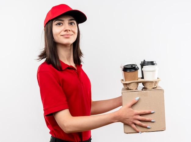 白い背景の上に立っている顔に笑顔でカメラを見て赤い制服とキャップ保持ボックスパッケージとコーヒーカップを身に着けている若い配達の女の子
