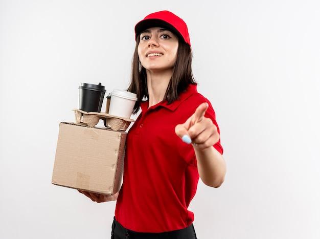 빨간 유니폼과 모자를 들고 젊은 배달 소녀 검지 손가락으로 흰 벽 위에 서있는 행복한 얼굴로 미소를 가리키는 상자 패키지와 커피 컵을 들고