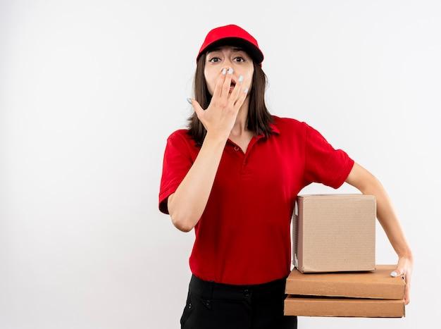 Молодая доставщица в красной форме и кепке держит коробку с пакетом и коробки для пиццы, глядя в камеру, потрясенная, прикрывая рот рукой, стоящей на белом фоне