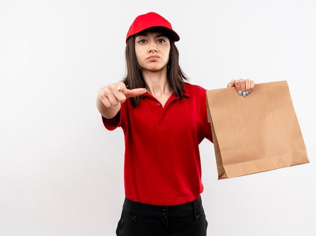 Молодая доставщица в красной форме и кепке держит бумажный пакет, указывая указательным пальцем на камеру, глядя с серьезным лицом, стоящим на белом фоне