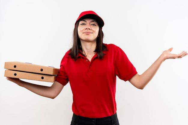 赤い制服を着た若い配達の女の子と白い壁の上に立っている側に腕を広げて混乱している笑顔のピザの箱を保持している
