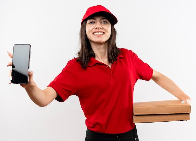 白い背景の上に立っているカメラを見て元気に笑顔のスマートフォンを示すピザの箱を保持している赤い制服と帽子を身に着けている若い配達の女の子