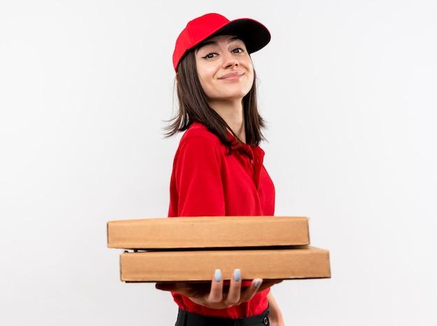 白い壁の上に立っている幸せそうな顔で笑顔のピザの箱を保持している赤い制服と帽子を身に着けている若い配達の女の子