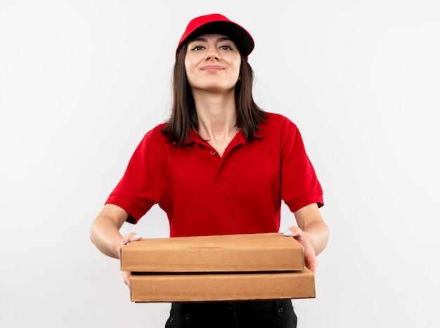 빨간 유니폼과 모자를 입고 젊은 배달 소녀 흰색 벽 위에 서 행복 한 얼굴로 웃 고 피자 상자를 들고