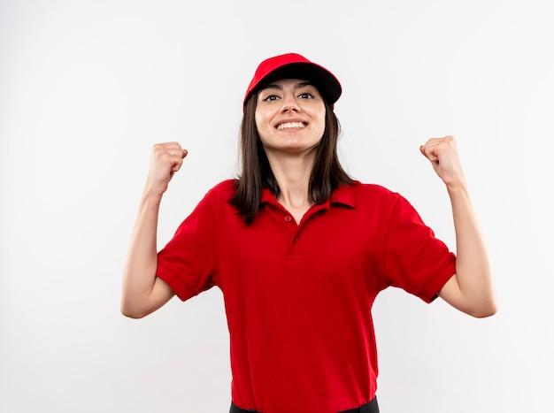 빨간색 유니폼과 모자를 입고 젊은 배달 소녀 흰색 배경 위에 유쾌하게 서 웃고 행복하고 흥분된 주먹을 떨리는 카메라를보고