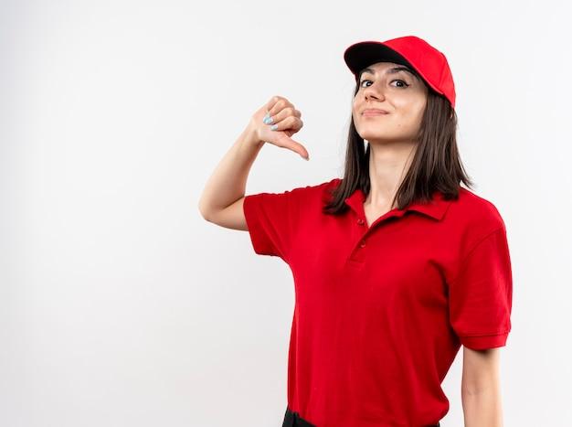 빨간 제복을 입고 젊은 배달 소녀와 흰 벽 위에 자신감 서 웃고 자신을 가리키는 모자