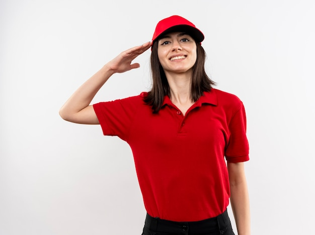 Молодая доставщица в красной форме и кепке салютует и уверенно улыбается, стоя над белой стеной