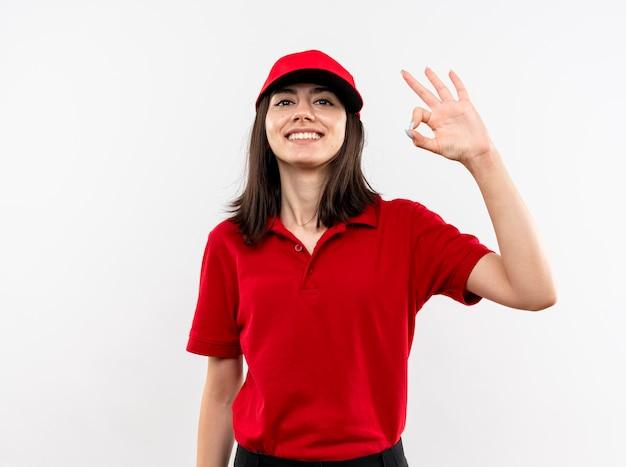 빨간 유니폼을 입고 젊은 배달 소녀와 흰 벽 위에 서있는 확인 서명을 보여주는 행복한 얼굴로 웃고 모자