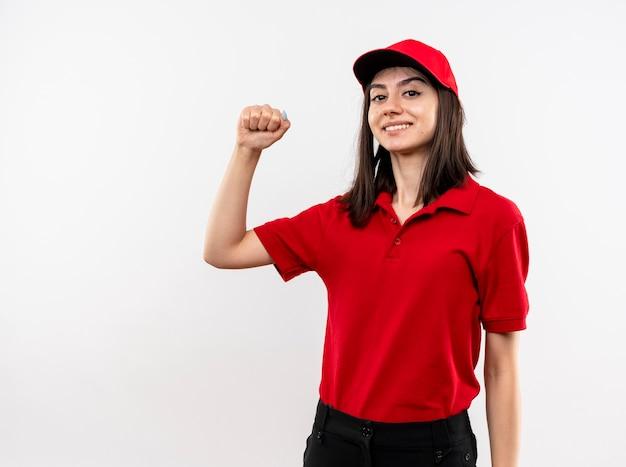 Giovane ragazza di consegna che indossa l'uniforme rossa e il berretto che stringe il pugno felice e positivo sorridente fiducioso in piedi sul muro bianco