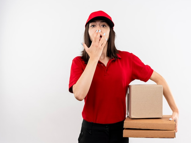 Giovane ragazza delle consegne che indossa l'uniforme rossa e il cappuccio che tiene il pacchetto della scatola e scatole per pizza guardando la telecamera essendo scioccato che copre la bocca con la mano in piedi su sfondo bianco