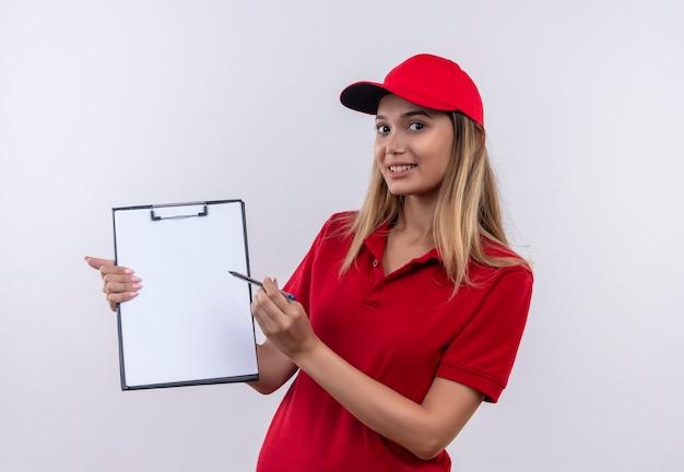 Giovane ragazza di consegna che indossa l'uniforme rossa e berretto che tiene appunti e penna isolato sul muro bianco