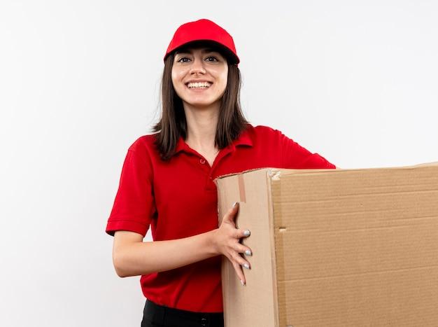 Giovane ragazza di consegna che indossa l'uniforme rossa e cappuccio che tiene grande scatola di cartone con il sorriso sul viso in piedi sopra il muro bianco