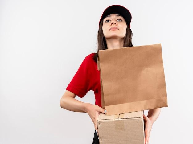 Giovane ragazza di consegna che indossa l'uniforme rossa e il cappuccio che tiene il pacchetto di carta e la scatola di cartone che guarda l'obbiettivo con espressione sicura che sta sopra fondo bianco