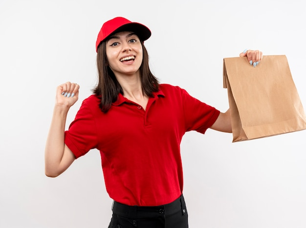 Giovane ragazza di consegna che indossa l'uniforme rossa e la protezione che tiene il pugno di serraggio del pacchetto di carta felice ed eccitato che sta sopra fondo bianco