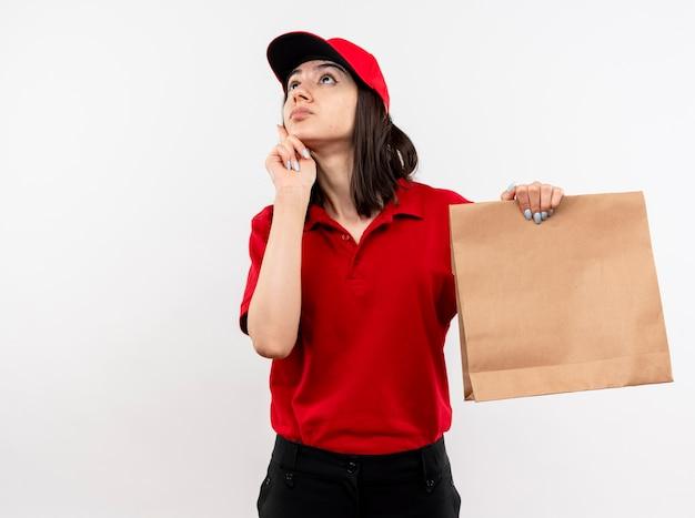 Giovane ragazza di consegna che indossa l'uniforme rossa e il cappuccio che tiene il pacchetto di carta che osserva in su in piedi perplesso sopra il muro bianco
