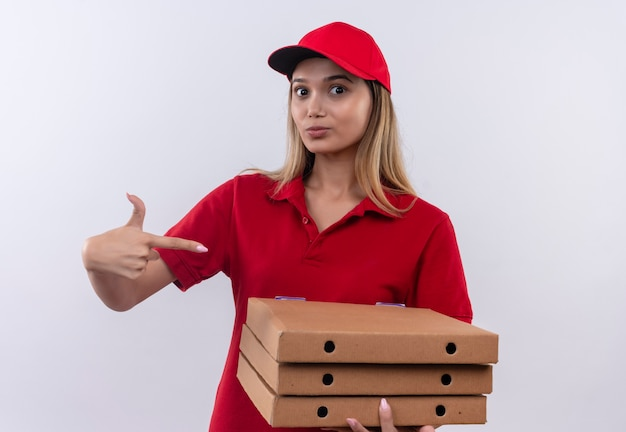 Young delivery girl wearing red uniform and cap holding and points to pizza boxes  isolated on white wall