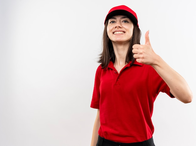 Young delivery girl wearing red uniform and cap lookign at camera smiling with happy face showing thumbs up standing over white background