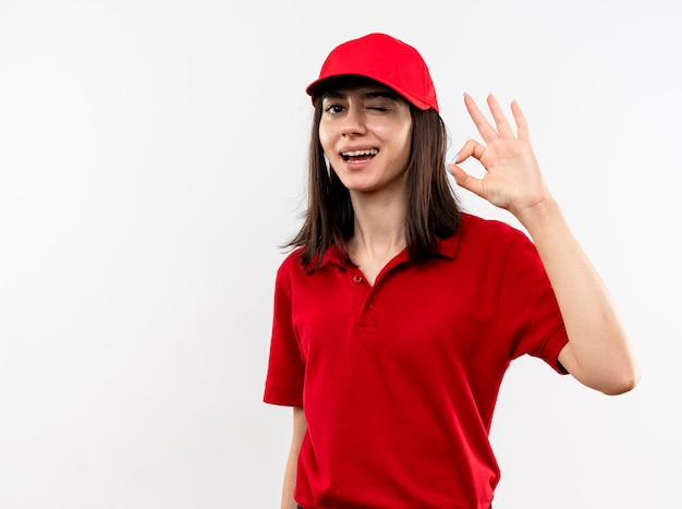 Young delivery girl wearing red uniform and cap lookign at camera smiling with happy face winking showing ok sign standing over white background