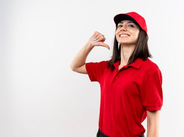 Giovane ragazza delle consegne che indossa l'uniforme rossa e il cappuccio che punta a se stessa sorridente fiducioso in piedi sopra il muro bianco