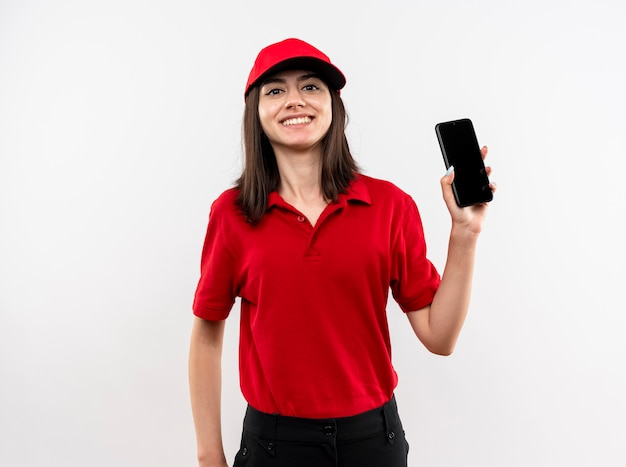 Young delivery girl wearing red uniform and cap showing smartphone smiling cheerfully standing over white wall