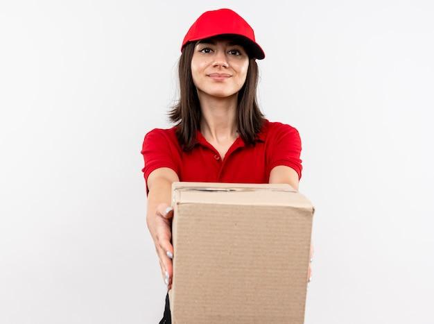Giovane ragazza di consegna che indossa l'uniforme rossa e cappuccio che allunga fuori il pacchetto della scatola che sorride amichevole che si leva in piedi sopra la parete bianca
