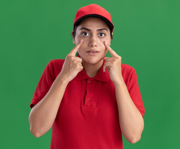 Young delivery girl  wearing uniform and cap pulling down eye lids isolated on green wall