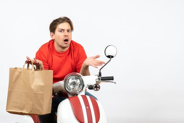 Giovane fattorino in uniforme rossa che si siede sul motorino che tiene il sacchetto di carta e che mostra la sua sorpresa sul muro bianco