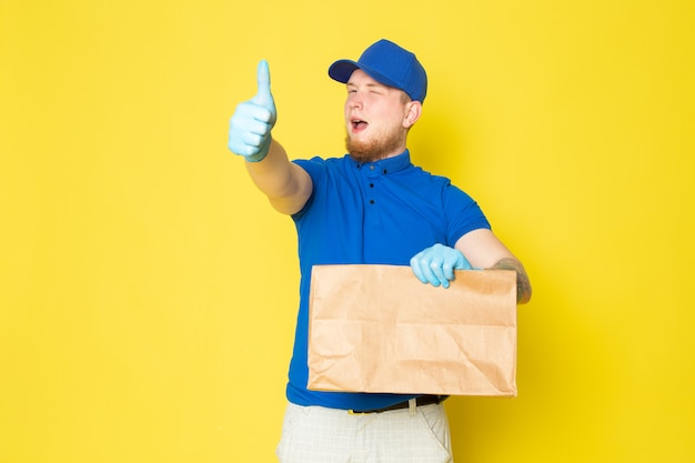 Young delivery man in blue polo blue cap white jeans backpack holding boxes on yellow
