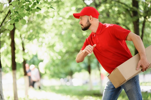 Young delivery man carrying cardboard box