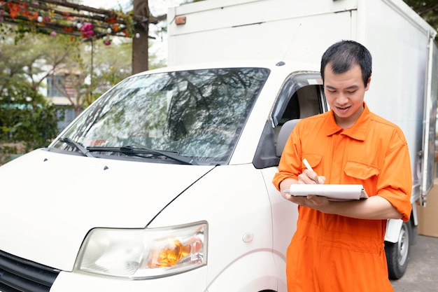 Young delivery man checking information about delivery
