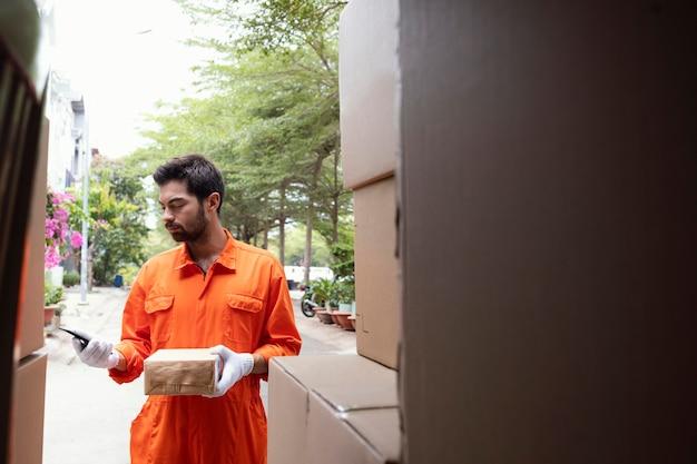 小包に関する情報をチェックする若い配達人