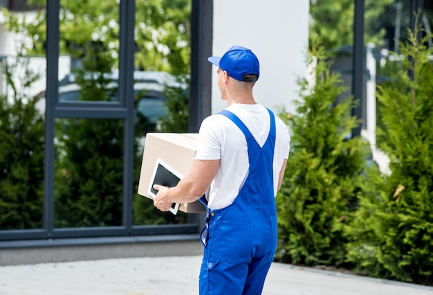 若い配達人は彼の手で段ボール箱を持っています