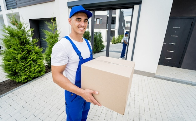 Young delivery man hold a cardboard box in his hands
