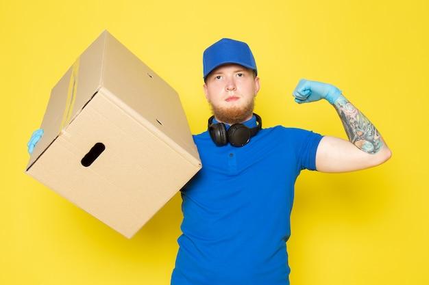 Молодой доставщик в голубой поло синяя кепка белый джинсовый рюкзак держит коробку на желтом