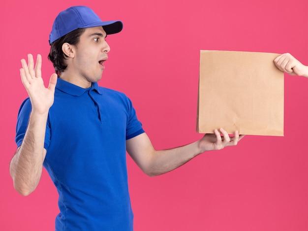 파란색 유니폼을 입은 젊은 배달원과 분홍색 벽에 격리된 모자