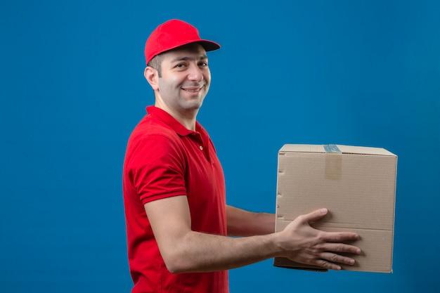Молодой доставщик в красной рубашке поло и кепке держит картонную коробку, давая клиенту улыбаться дружелюбно над голубой стене