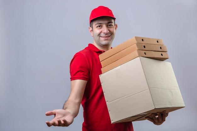 Молодой доставщик в красной рубашке поло и кепке держит картонные коробки, улыбаясь, делая жест рукой, ожидая оплаты через изолированную белую стену