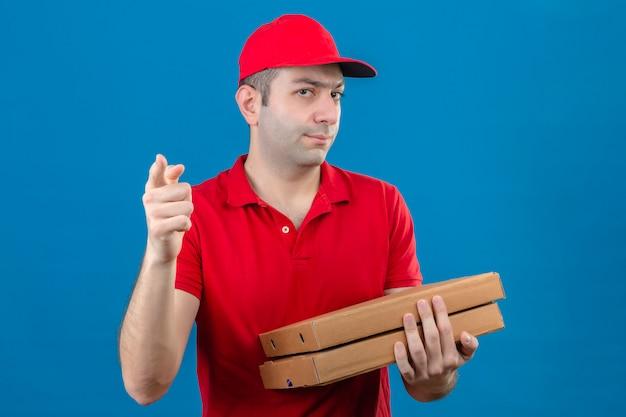 赤いポロシャツと帽子をかざしてカメラを非難し、孤立した青い壁の上に指を指してピザの箱を保持している若い配達人