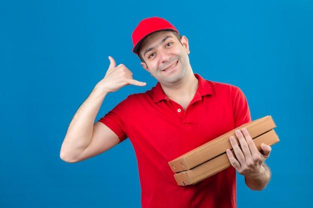 Молодой доставщик в красной рубашке поло и кепке держит коробки для пиццы, заставляя называть меня жестом, дружелюбно улыбаясь синей стене