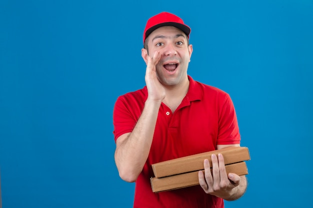 赤いポロシャツとピザの箱を持って若い配達人が分離された青い壁に元気に笑って口の近くの手で誰かを検索する名前を叫んでいるピザの箱を保持