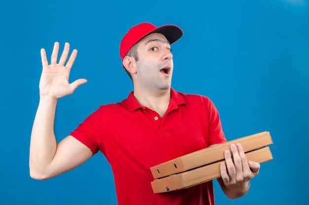 Молодой доставщик в красной рубашке поло и кепке держит коробки для пиццы, размахивая рукой, глядя удивленно на изолированной синей стене