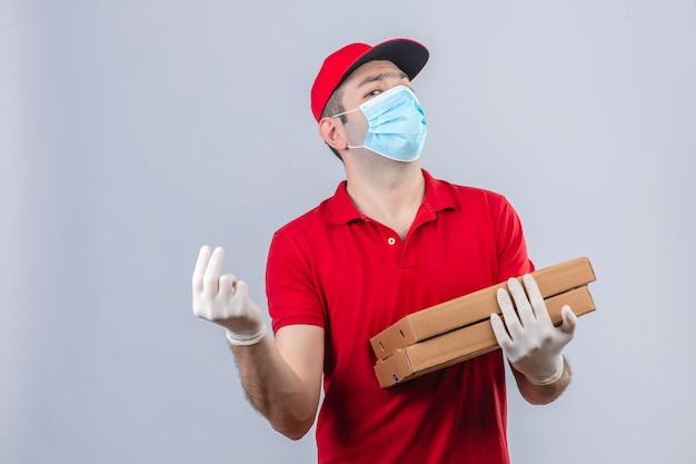 Молодой доставщик в красной рубашке поло и кепке в медицинской маске, держащей коробки для пиццы, жестикулируя рукой и пальцами, делая жест денег, ожидая оплаты, недовольной изолированной белой предпосылкой