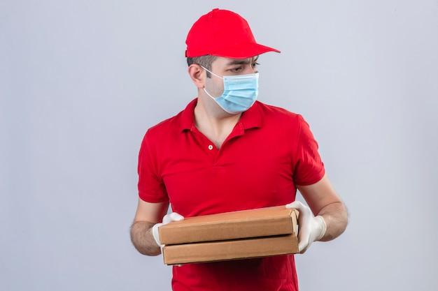 Молодой доставщик в красной рубашке поло и кепке в медицинской маске держит коробки для пиццы, глядя со страхом на изолированную белую стену