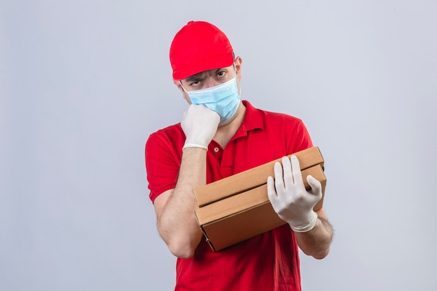 赤いポロシャツの若い配達人と交差した腕とあごに手を上げた顔で立っている顔にピザの箱懐疑的で神経質な不承認の式を保持している医療マスクのキャップ